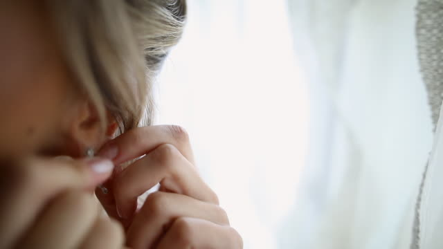 young woman putting on earrings before wedding while standing near window - earring stock videos & royalty-free footage