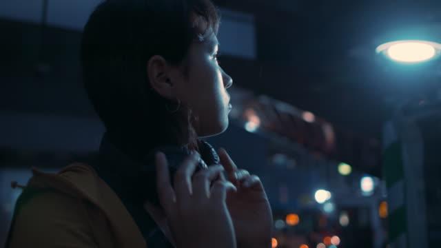 vidéos et rushes de young woman putting on headphones in rain at night in tokyo, japan - casque audio