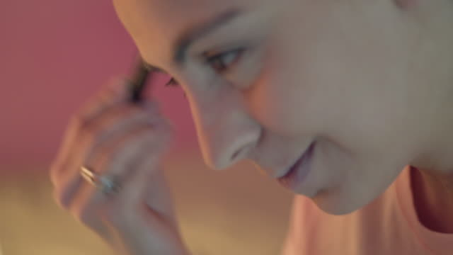 young woman putting on her make up in bedroom - full hd format stock videos & royalty-free footage