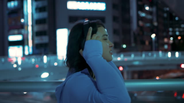 Young Woman putting on hoodie and headphones, smiling, stretching at night in Tokyo, Japan