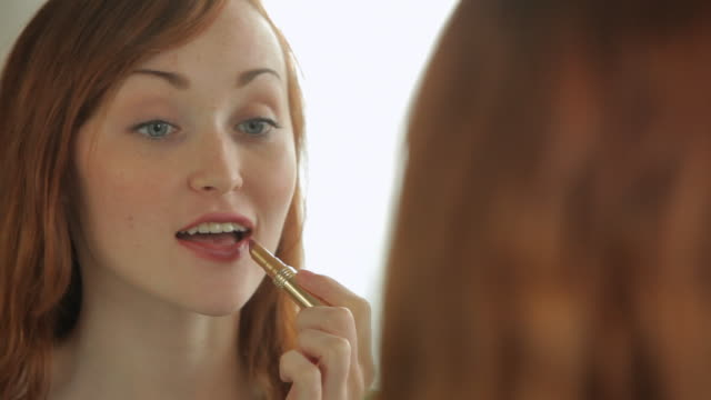 cu young woman putting on lipstick in mirror and smiling - lipstick stock videos & royalty-free footage