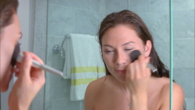 vidéos et rushes de cu young woman putting on makeup in bathroom mirror, new york city, new york, usa - mascara
