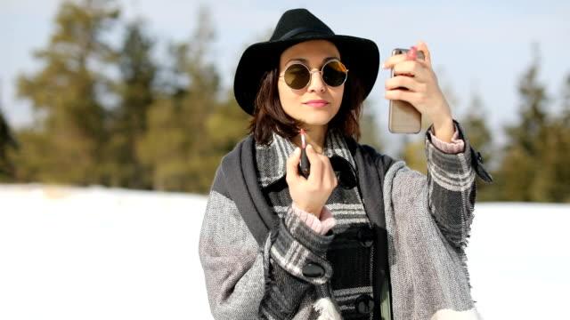vídeos y material grabado en eventos de stock de mujer joven poniendo maquillaje en invierno - pintalabios
