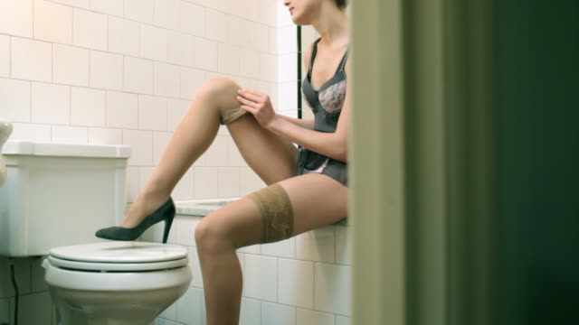 stockvideo's en b-roll-footage met young woman putting on stockings in bathroom - panty