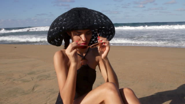 young woman putting on sunglasses on beach - sonnenhut stock-videos und b-roll-filmmaterial