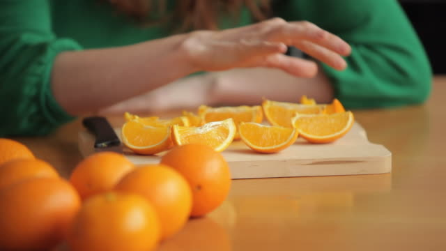 CU TU Young Woman Putting Orange Slice in Her Mouth and Smiling
