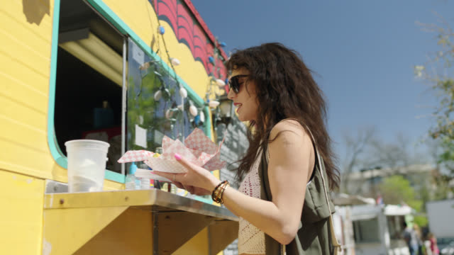 stockvideo's en b-roll-footage met young woman raises her hand when her order is called and walks up to food truck window to pick up her food. - picknick