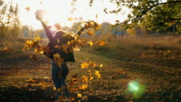 Young woman raising her hands and spinning around scattering autumn leaves. Happy girl showing joyful emotions with sunset at background. Lady enjoying beautiful autumn environment. Slow motion Close up
