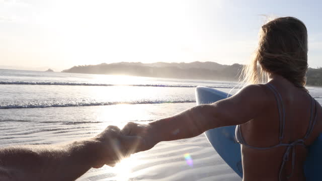 vídeos de stock e filmes b-roll de young woman reaches for man's hand while standing in gentle surf - imagem em movimento