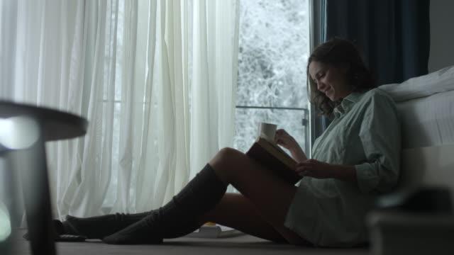 Jeune femme lisant un livre et boire du café