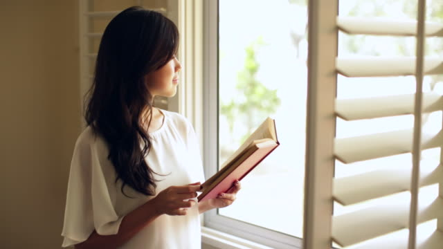 MS Young woman reading a book and looking out of the window