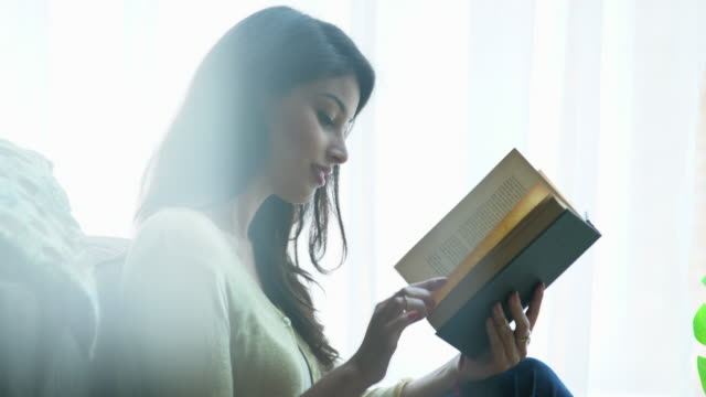 cu young woman reading a book at home. - sitting点の映像素材/bロール