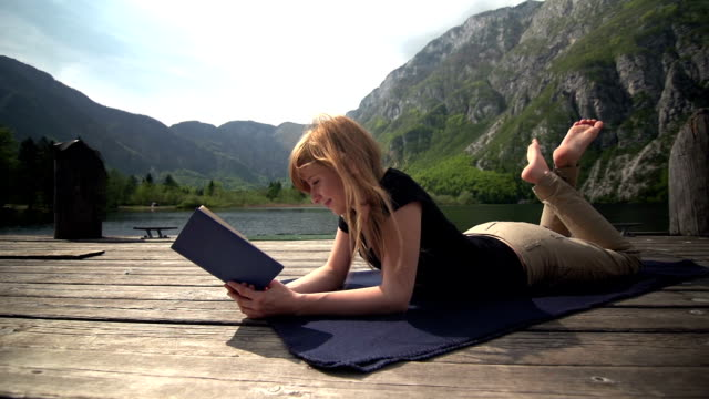 Young woman reading a book by a lake in mountains