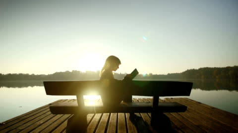 stockvideo's en b-roll-footage met young woman reading a book by the lake - study
