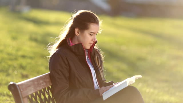 Young woman reading a book by the park
