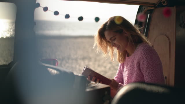 ms young woman reading a book in her camper van - sonnig stock-videos und b-roll-filmmaterial