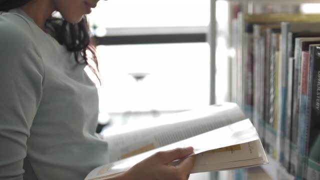 図書館で本を読んでいる若い女性、本の教育を読む - 公共図書館点の映像素材/bロール