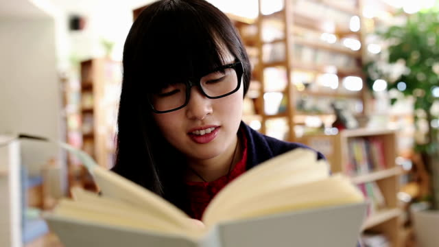 Young woman reading a book in the library