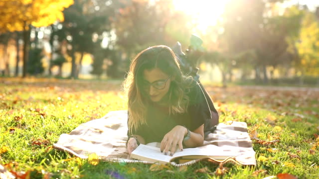 Jonge vrouw lezen van een boek in het park