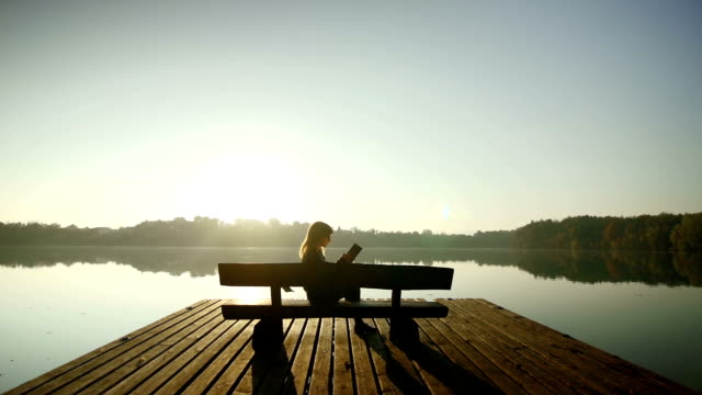 young woman reading a book on a bench by lake - magazine stock videos & royalty-free footage