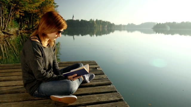 Young woman reading a book on a pier by lake
