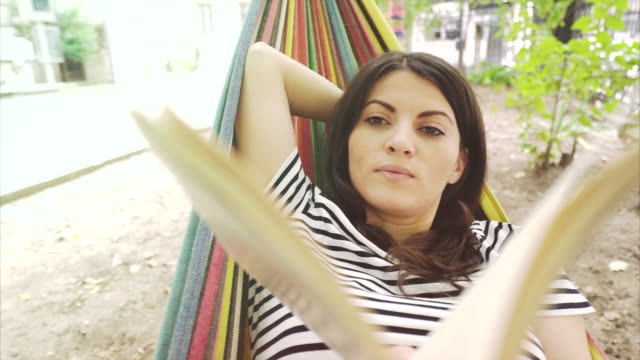 young woman reading a book on hammock. - woman hands behind head stock videos & royalty-free footage