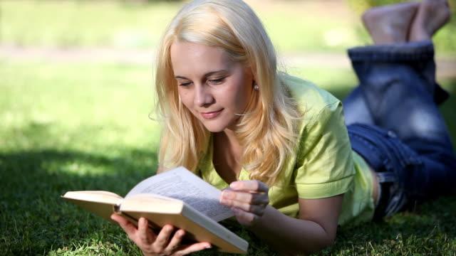 vídeos de stock e filmes b-roll de jovem ler um livro - olhar de lado