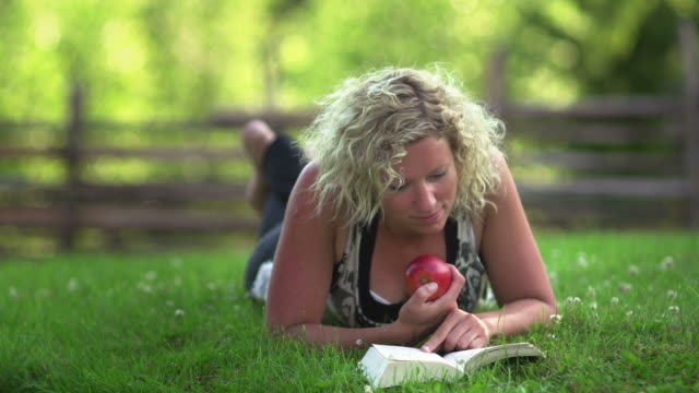 young woman reading a book - grass family stock videos and b-roll footage