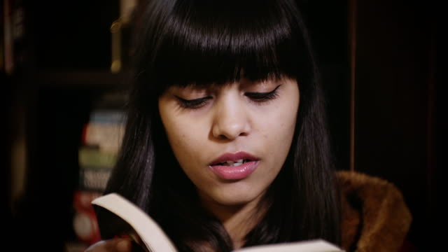 young woman reading a book. - bookshelf stock videos and b-roll footage