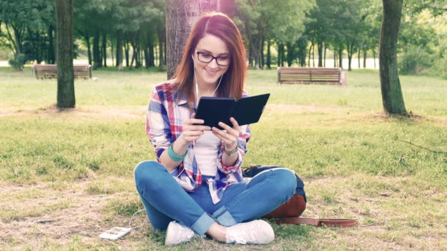 Young woman reading an e-book among nature