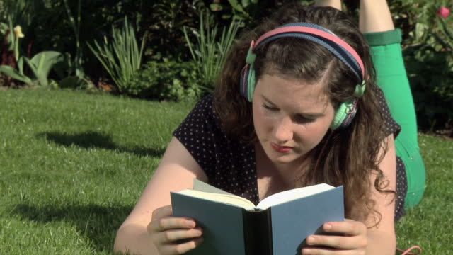 HD DOLLY: Young woman reading and listening music at park