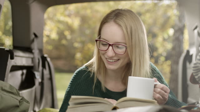 Young woman reading book and drink coffee in back of the car