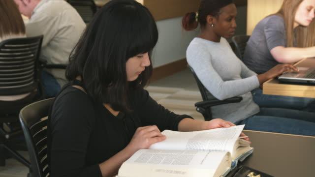 vídeos y material grabado en eventos de stock de cu ds young woman reading book at library, orem, utah, usa - orem