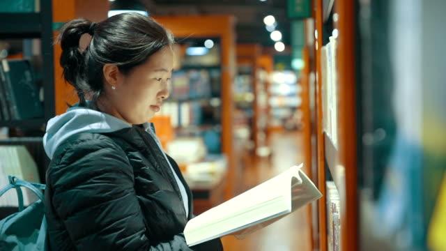 図書館で本を読む若い女性 - 公共図書館点の映像素材/bロール
