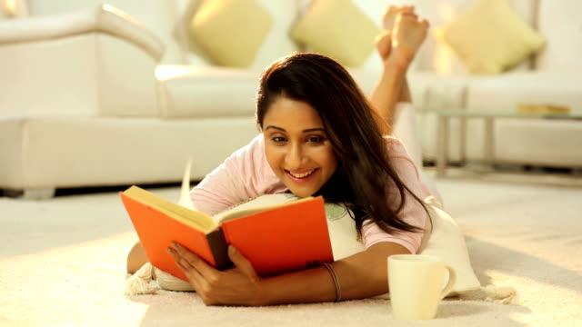 vídeos y material grabado en eventos de stock de ms pan young woman reading book in living room - planta del pie