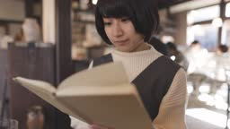 Young woman reading book in old Japanese style restaurant