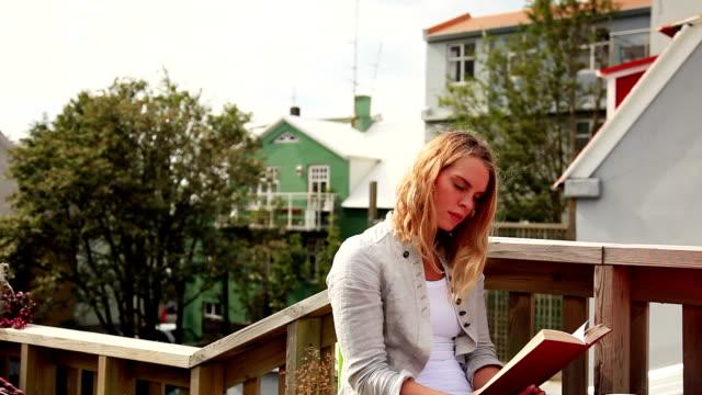 vidéos et rushes de ms young woman reading book in outdoor coffee shop, reykjavik, iceland - seulement des jeunes femmes