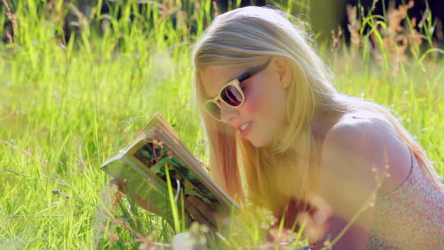 ms selective focus young woman reading book, lying in meadow / london, united kingdom - libro in brossura video stock e b–roll