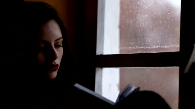 Young woman reading book near the window