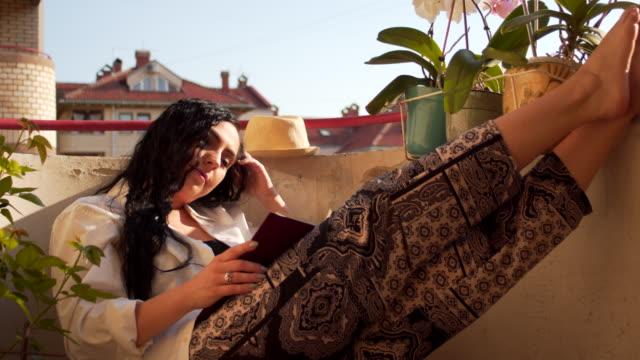 junge frau lesen buch auf balkon - balkon stock-videos und b-roll-filmmaterial