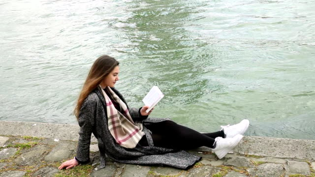 young woman reading book on seine river coastline - city break stock videos and b-roll footage