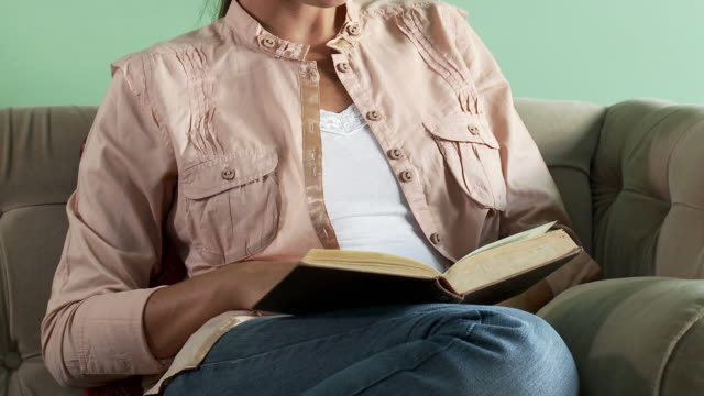 young woman reading book on sofa - hardcover book stock videos and b-roll footage