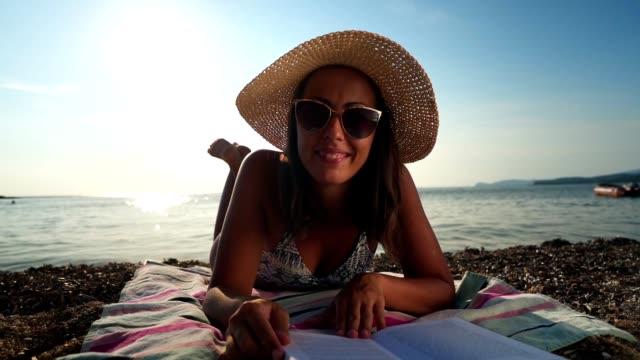 vídeos de stock, filmes e b-roll de jovem mulher lendo livro na praia - toalha de praia