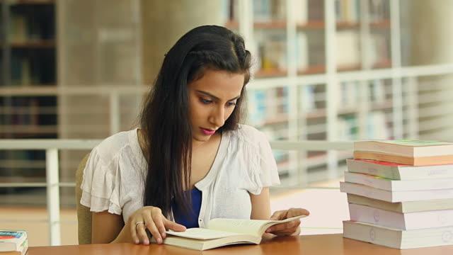 young woman reading books, noida, uttar pradesh, india - gestapelt stock-videos und b-roll-filmmaterial