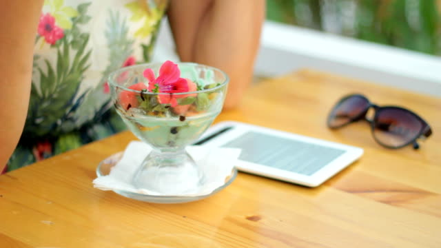 young woman reading e-reader, eating ice cream