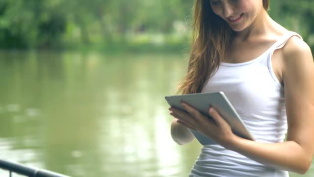 Jonge vrouw lezen van e-lezer buiten in park