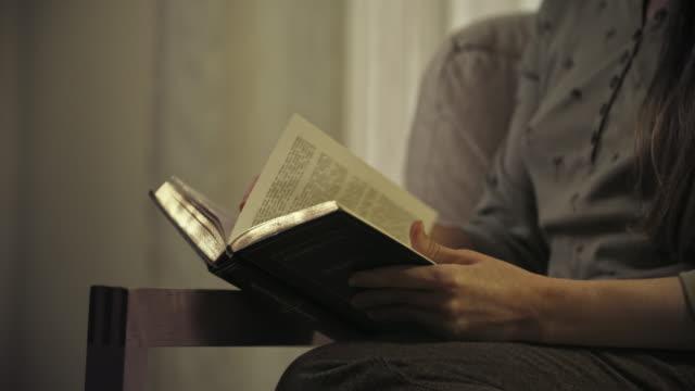 vídeos de stock, filmes e b-roll de young woman reading in arm chair. - pouca luz