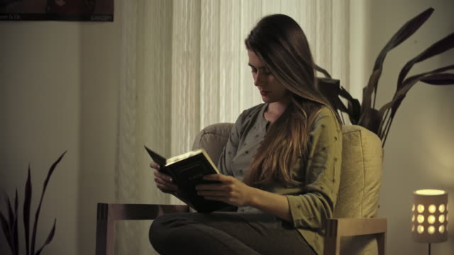 young woman reading in arm chair. - low lighting stock videos & royalty-free footage
