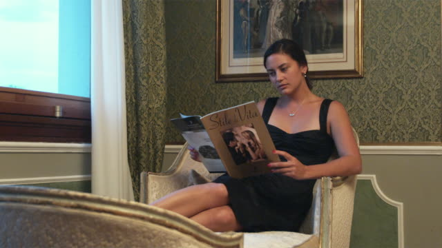 MS DS. Young woman reading in chaise longue / Venice, Italy