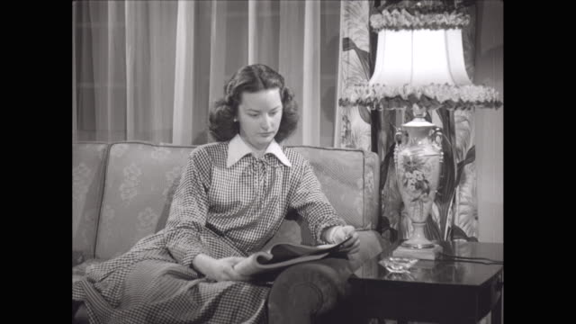 ms zi young woman reading magazine on sofa in living room / united states - magazine stock videos & royalty-free footage